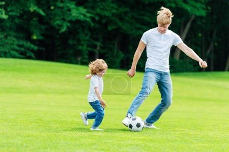 Photo pour Heureux père et fils, jouer au soccer sur l'herbe verte dans le parc - image libre de droit