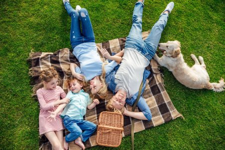 Photo for Top view of happy young family with golden retriever dog resting on grass at picnic - Royalty Free Image