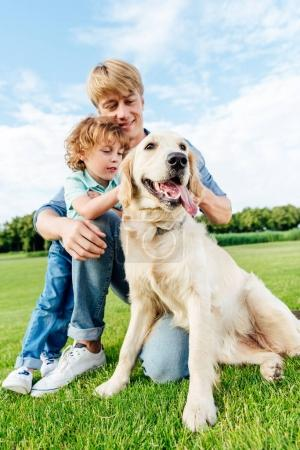 father and son with dog at park