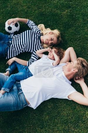 parents with son resting on grass