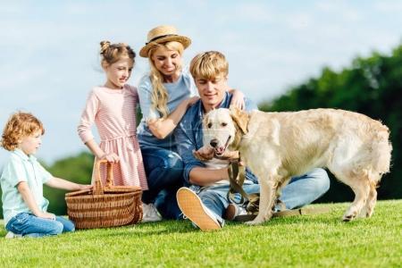 Photo pour Heureux jeune famille avec chien et panier de pique-nique reposant sur la prairie verte dans le parc - image libre de droit