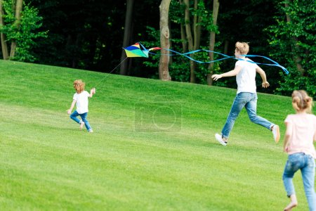 Photo for Happy father with daughter and son playing with kite while running on green meadow in park - Royalty Free Image