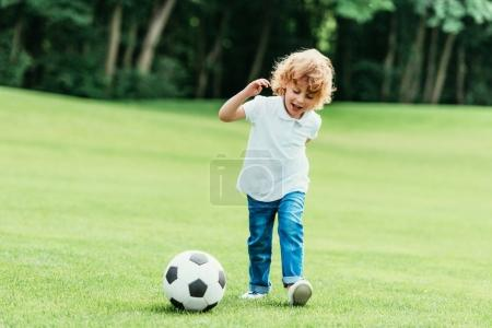 Boy playing soccer in park