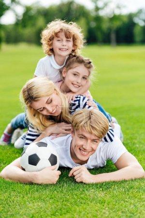 Photo pour Heureux jeune famille avec ballon de football couché sur la pelouse verte au parc - image libre de droit
