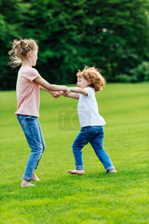 Photo for Cute little brother and sister holding hands while playing on green grass in park - Royalty Free Image