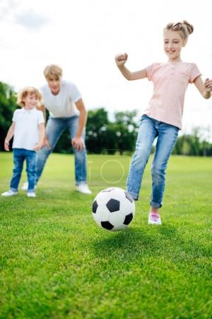 Photo for Father with son looking at cute little girl kicking soccer ball on meadow - Royalty Free Image