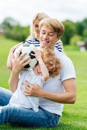 Photo pour Heureux jeune famille avec un enfant qui joue avec le ballon de football sur la pelouse - image libre de droit