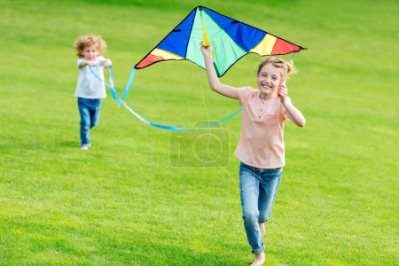 Siblings playing with kite at park