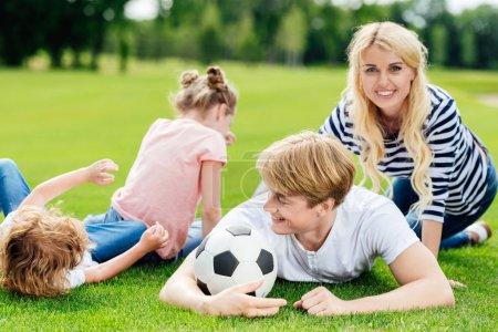 Photo pour Heureux jeune famille avec deux enfants s'amusant avec ballon de soccer au parc - image libre de droit