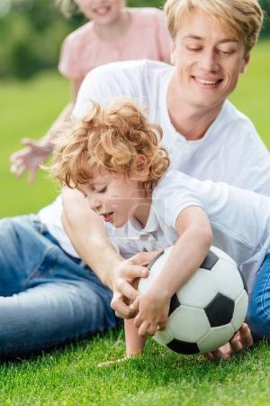 Photo pour Heureux père et fils, jouer avec le ballon de soccer sur l'herbe verte au parc - image libre de droit