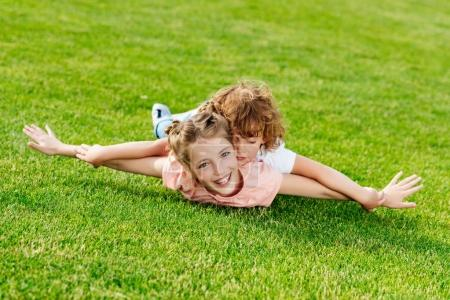 Photo for Adorable brother and sister with arms outstretched lying on green grass in park - Royalty Free Image