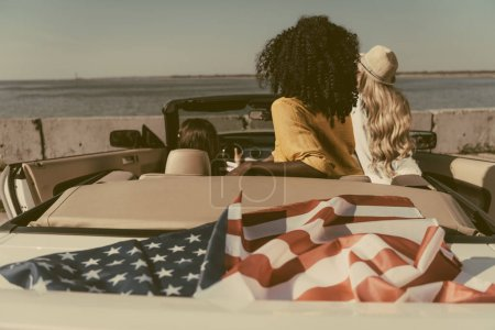 Friends sitting in car with american flag