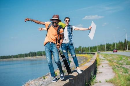 Foto de Hombres multiculturales con cartulina vacía caminando por el parapeto mientras autostop juntos - Imagen libre de derechos