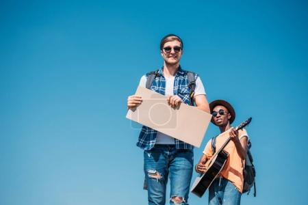 Multiethnic men with empty cardboard hitchhiking