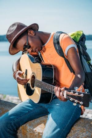 Photo pour Portrait de jeune homme afro-américain assis sur le parapet et jouer de la guitare - image libre de droit