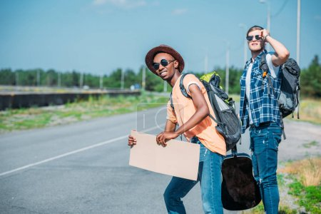 multiethnic men with cardboard hitchhiking