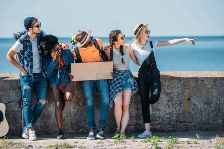 Photo for Multiethnic young friends with guitar and empty cardboard pointing away while hitchhiking together - Royalty Free Image