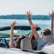 Young couple with outstretched arms sitting in car...