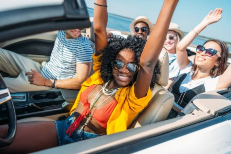 Photo for Multiethnic smiling friends riding car while traveling together - Royalty Free Image