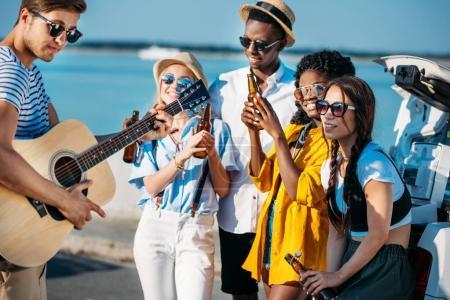 Foto de Grupo multiétnico de amigos bebiendo cerveza mientras pasan tiempo juntos en la playa - Imagen libre de derechos