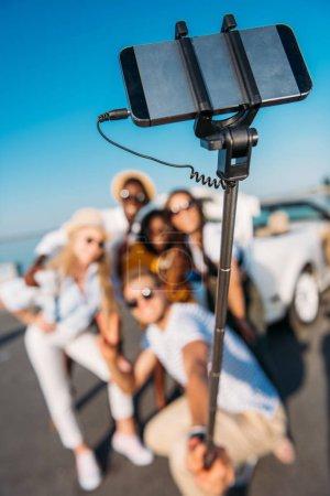 Foto de Enfoque selectivo de multiétnicos amigos felizes tomando selfie juntos en smartphone - Imagen libre de derechos