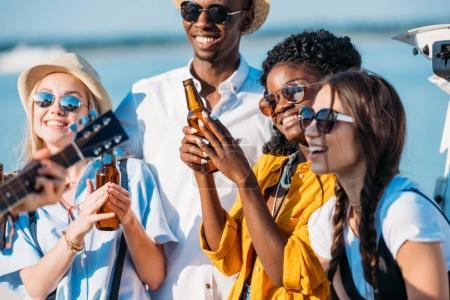 Foto de Multiétnicos alegres amigos bebiendo cerveza y pasar tiempo juntos - Imagen libre de derechos