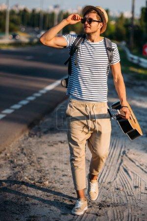Photo pour Jeune homme à la guitare, marchant le long de la route tout en faisant de l'auto-stop seul - image libre de droit