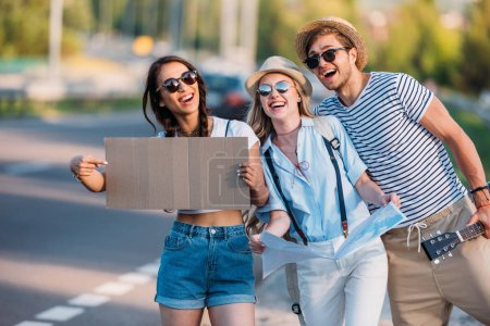 Photo for Multicultural friends with empty cardboard hitchhiking while traveling together - Royalty Free Image