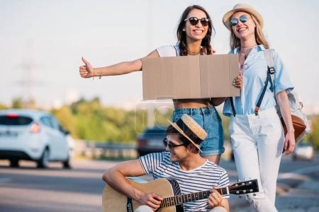 Foto de Amigos multiculturales con cartulina vacía autostop mientras viajan juntos - Imagen libre de derechos
