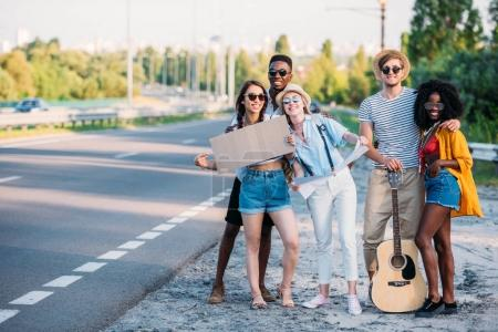 Photo for Multicultural group of young hitchhikers with map and empty cardboard standing at sidewalk of road - Royalty Free Image