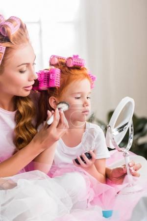 Mother and daughter doing makeup