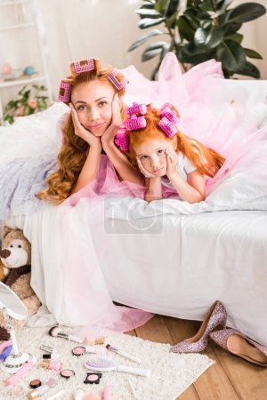 mother and daughter lying on bed
