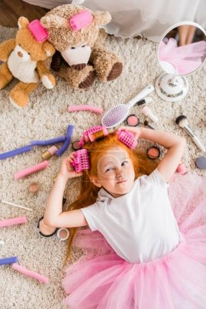 little girl with curlers on head