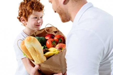 father and son with grocery bag