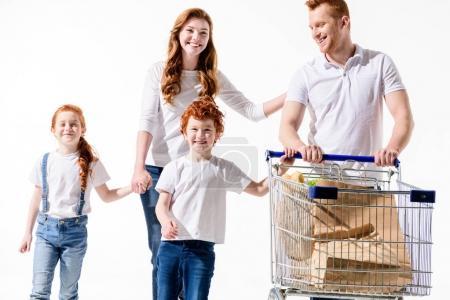 Photo pour Heureux rousse famille avec chariot marchant ensemble isolé sur blanc - image libre de droit