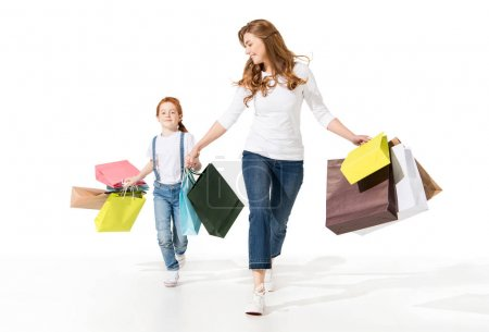 Photo for Happy young mother and cute little daughter holding shopping bags and walking together isolated on white - Royalty Free Image