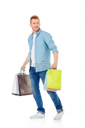 Photo pour Souriant jeune homme tenant des sacs en papier coloré et regardant loin isolé sur blanc - image libre de droit