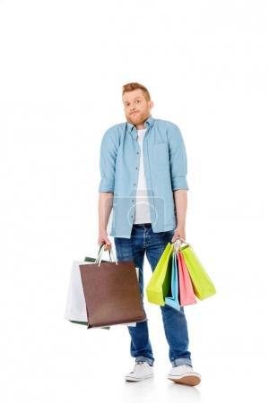 Photo pour Jeune rousse homme tenant des sacs à provisions colorés et regardant caméra isolé sur blanc - image libre de droit