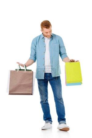 Photo pour Beau jeune homme tenant des sacs colorés isolés sur blanc - image libre de droit