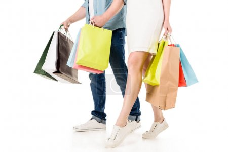 Photo for Cropped shot of young couple holding colorful paper bags and walking together isolated on white - Royalty Free Image