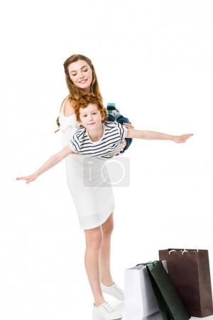 Photo pour Heureuse jeune mère tenant adorable petit fils en se tenant debout avec des sacs à provisions isolés sur blanc - image libre de droit