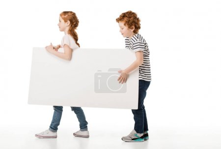 Photo for Side view of cute redhead siblings holding blank banner isolated on white - Royalty Free Image