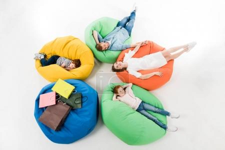 Photo for High angle view of young family with two kids resting on bean bag chairs after shopping - Royalty Free Image