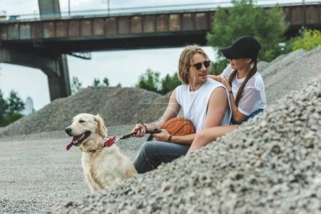 Photo pour Beau jeune couple avec chien et basket ball sur le tas de cailloux - image libre de droit