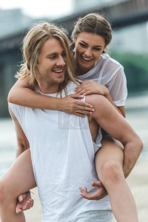Photo pour Belle femme piggybackking sur copain sur la plage - image libre de droit