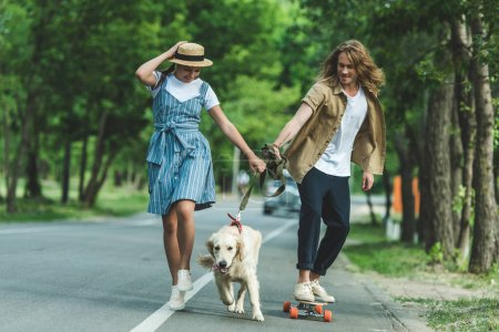 Photo for Happy young couple riding on board and walking with dog - Royalty Free Image