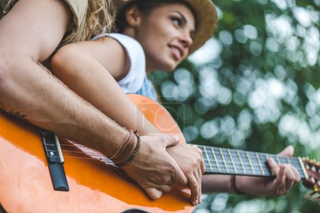 couple with guitar in park