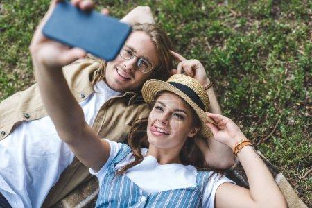 Photo pour Sourire jeune couple prendre selfie dans le parc - image libre de droit