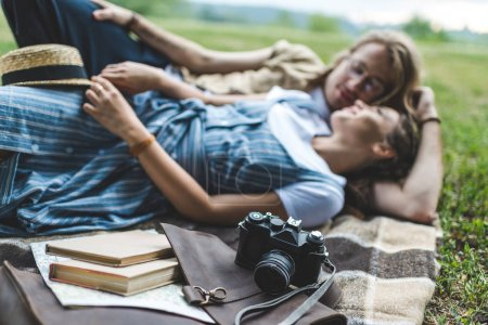 Photo for Beautiful young couple relaxing in park on plaid - Royalty Free Image