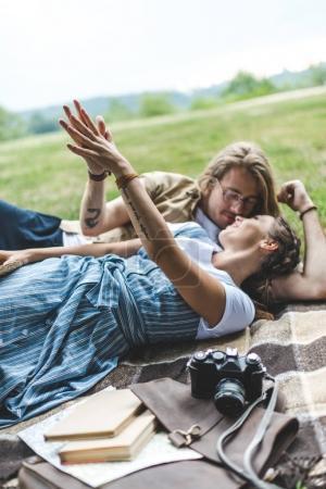 Photo pour Heureux jeune couple se détendre dans le parc sur carreaux - image libre de droit